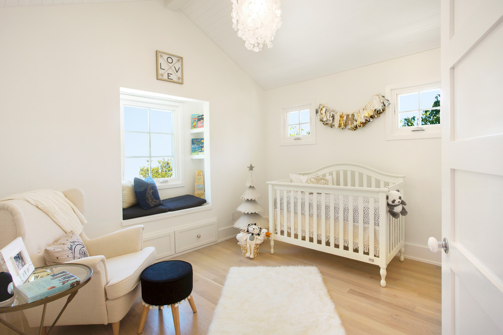 Example of a transitional gender-neutral light wood floor and beige floor nursery design in Other with white walls
