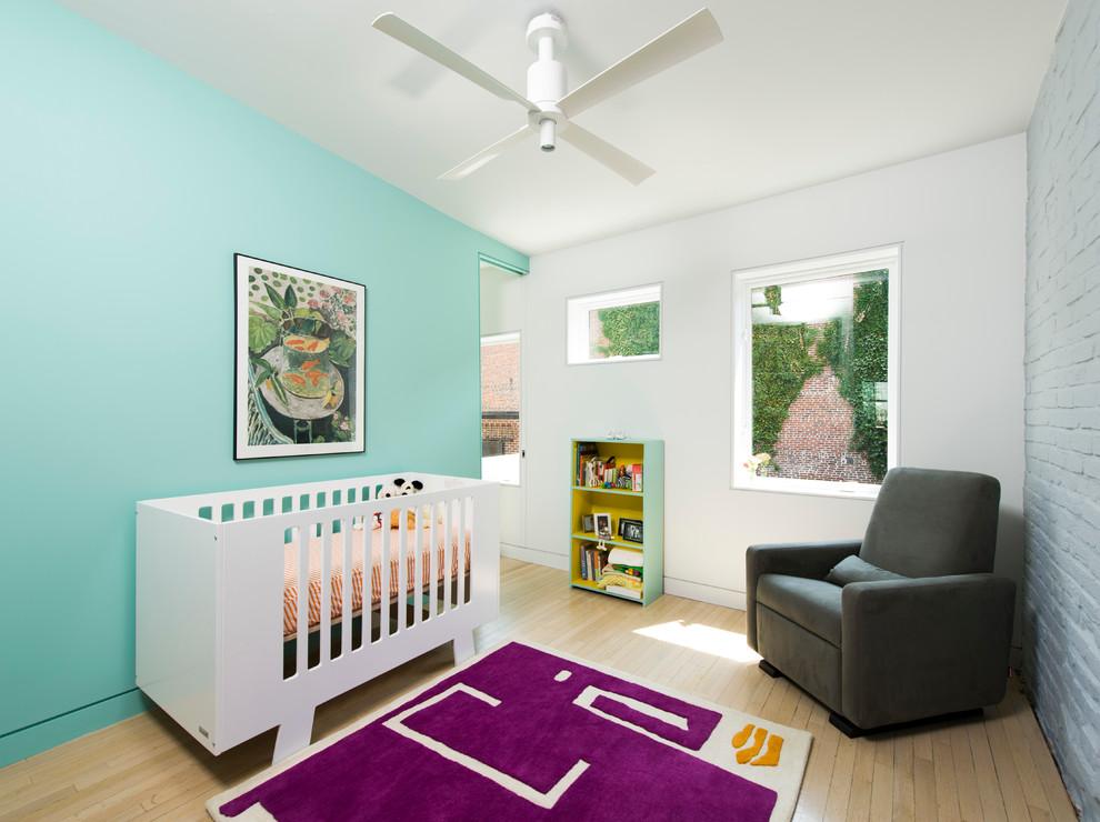 Nursery - mid-sized scandinavian gender-neutral light wood floor and beige floor nursery idea in DC Metro with blue walls