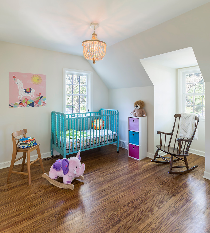Example of a mid-sized eclectic gender-neutral medium tone wood floor nursery design in Minneapolis with white walls