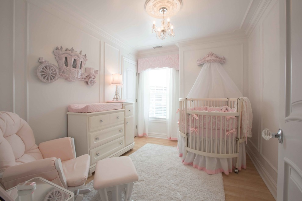 Example of a mid-sized classic laminate floor nursery design in Other with white walls