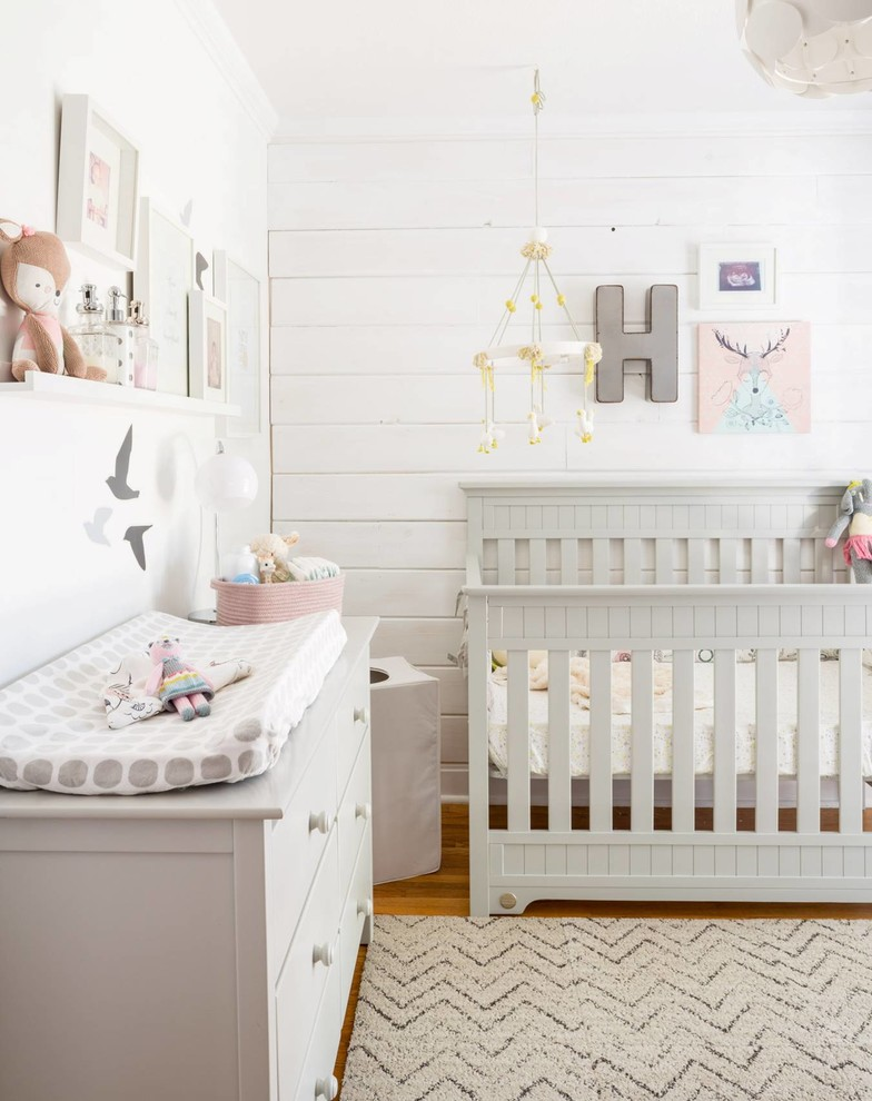 Example of a mid-sized farmhouse girl medium tone wood floor nursery design in Toronto with white walls