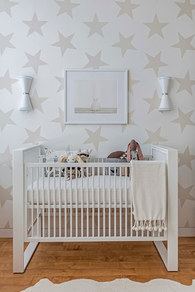 Design ideas for a contemporary gender-neutral nursery in New York with multi-coloured walls and light hardwood floors.