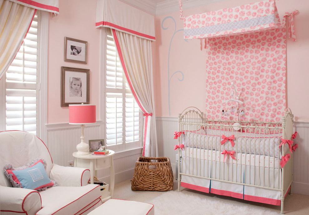 Inspiration for a mid-sized timeless girl carpeted nursery remodel in Wilmington with pink walls