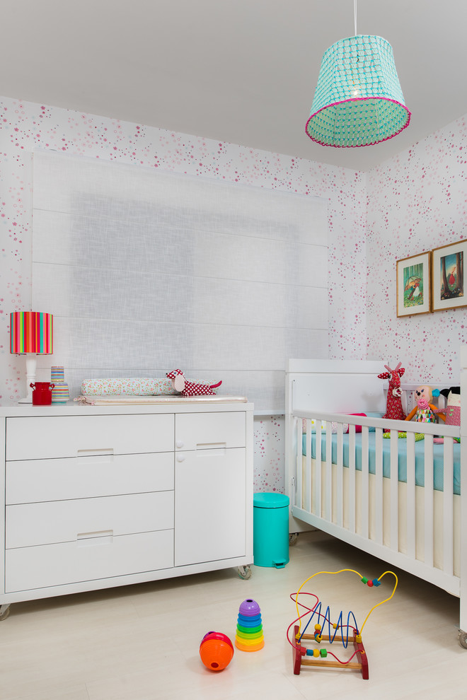 Example of a small trendy light wood floor and beige floor nursery design in Other with multicolored walls