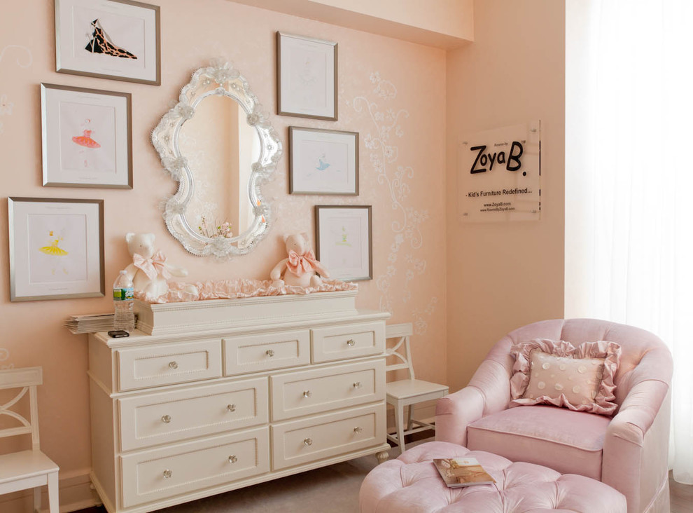Example of a classic girl medium tone wood floor nursery design in New York with pink walls