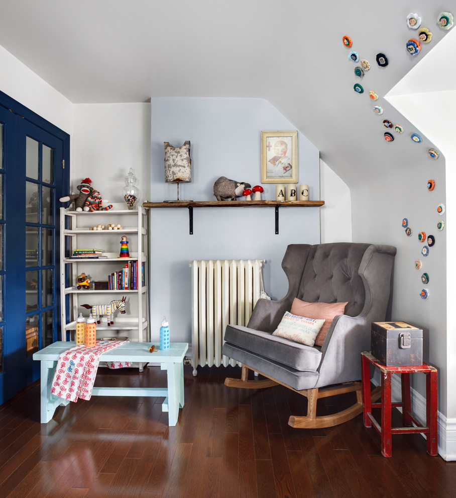 Example of a transitional gender-neutral dark wood floor nursery design in Toronto with blue walls
