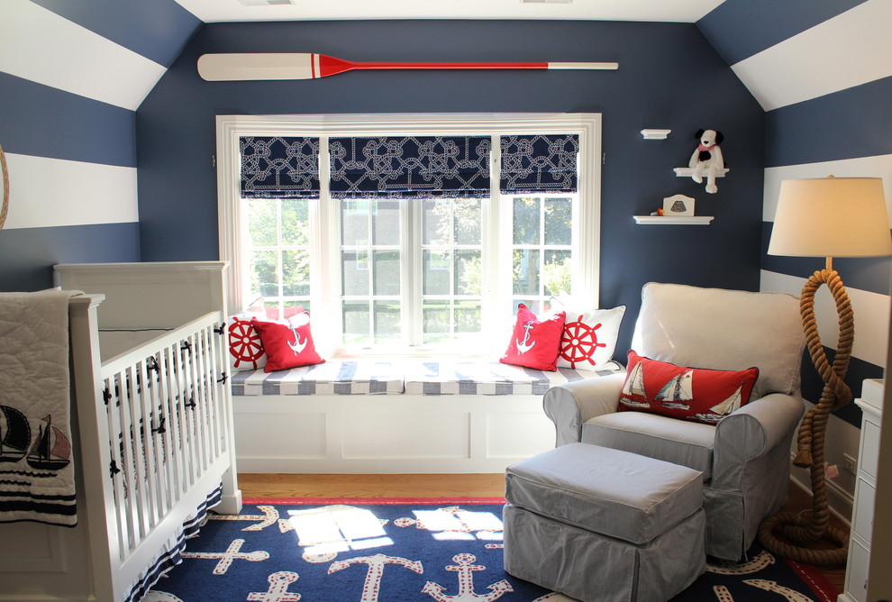 Inspiration for a small coastal boy medium tone wood floor nursery remodel in Chicago with blue walls