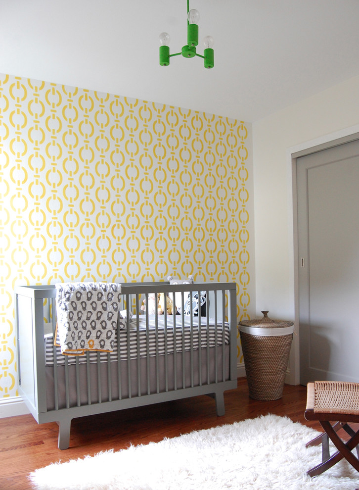 Example of a small trendy gender-neutral medium tone wood floor nursery design in San Francisco with yellow walls