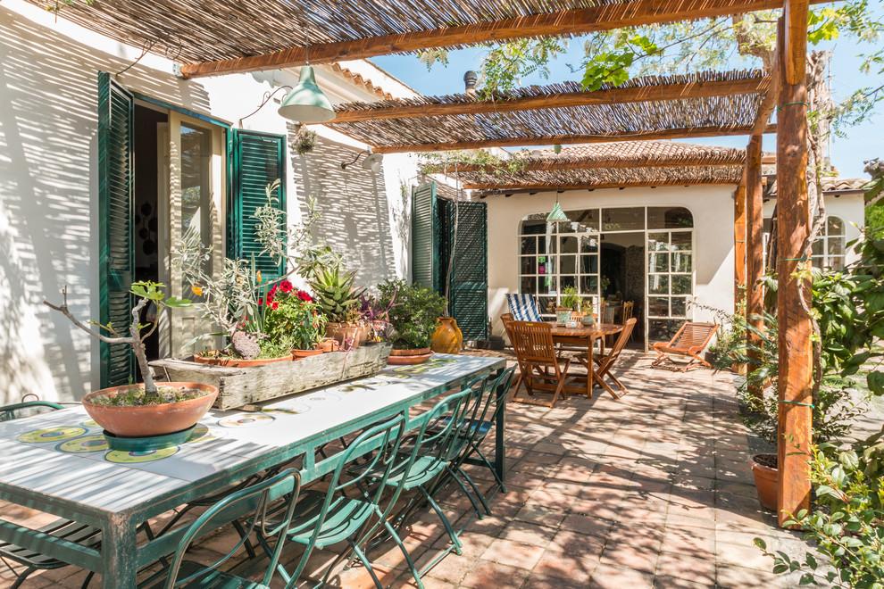 Tuscan brick patio container garden photo in Catania-Palermo with a pergola