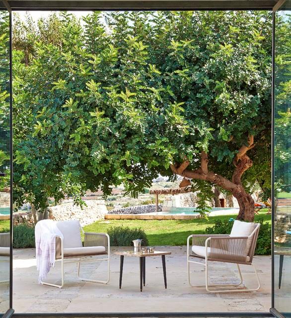 Ispirazione per un patio o portico mediterraneo di medie dimensioni e nel cortile laterale con pavimentazioni in pietra naturale