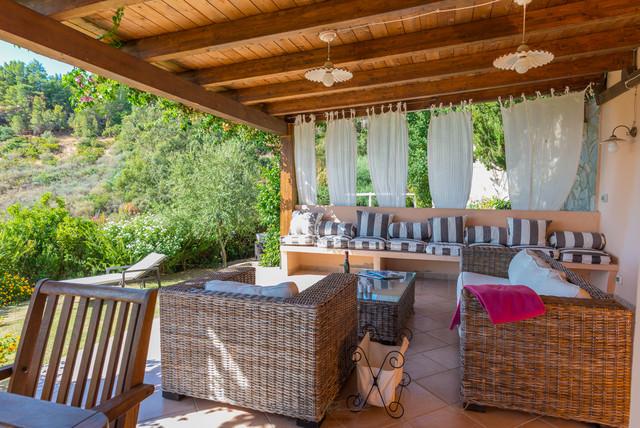 Foto di un patio o portico mediterraneo di medie dimensioni e dietro casa con piastrelle e un tetto a sbalzo