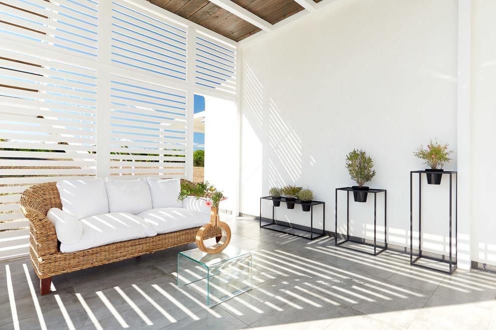 Foto di un patio o portico design con un tetto a sbalzo e pavimentazioni in cemento