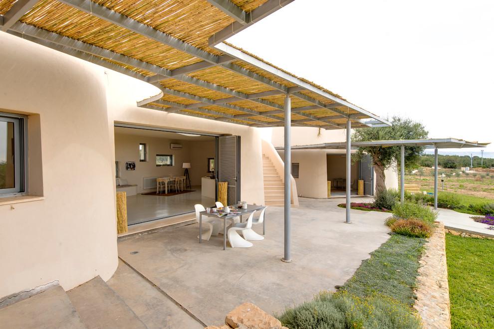 Esempio di un grande patio o portico mediterraneo con pavimentazioni in cemento e una pergola