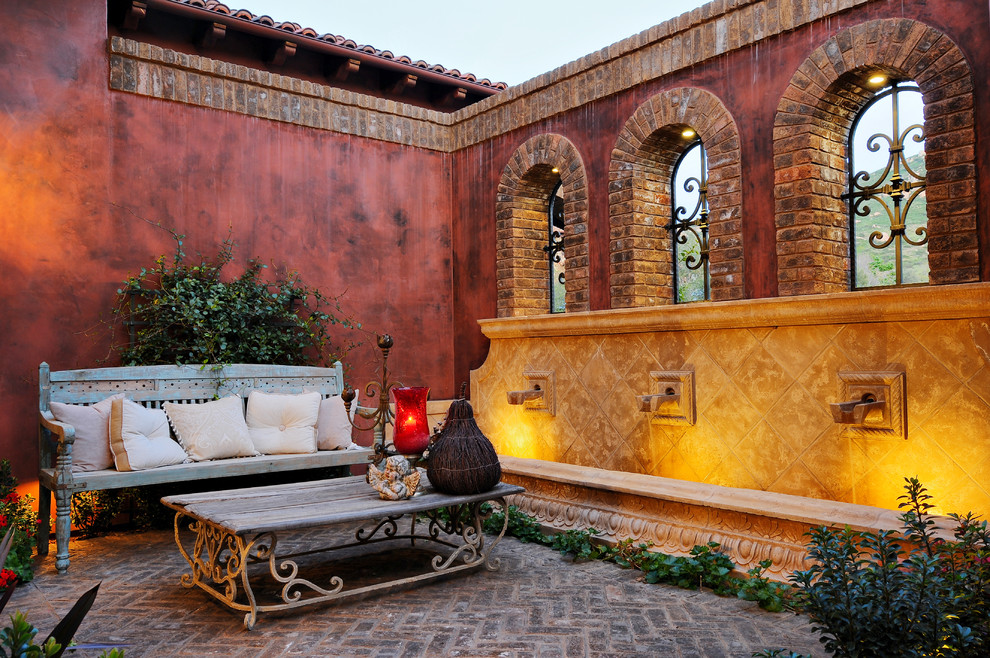 Example of a tuscan brick patio fountain design in San Diego