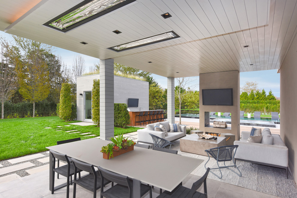 Inspiration for a huge contemporary backyard patio remodel in New York with a fireplace