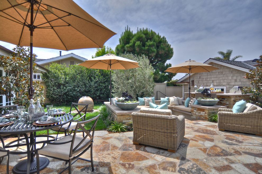 Example of a beach style stone patio design in Los Angeles with no cover