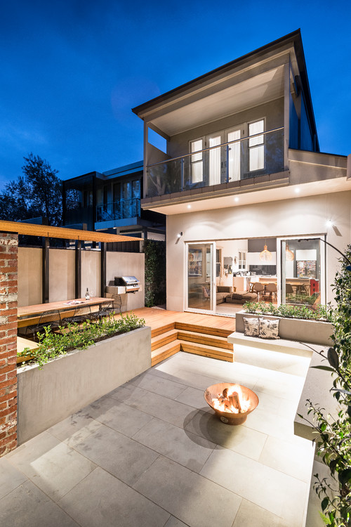 terracotta fire pit on paved outdoor area of modern home