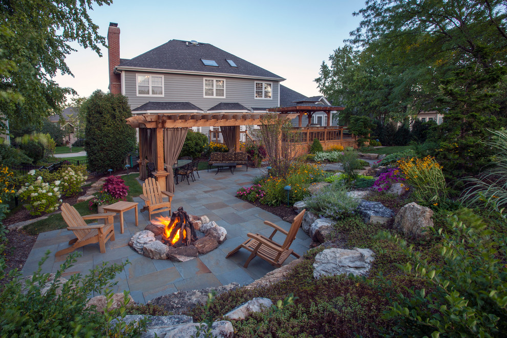 Example of a classic backyard stone patio design in Chicago with a fire pit and a pergola