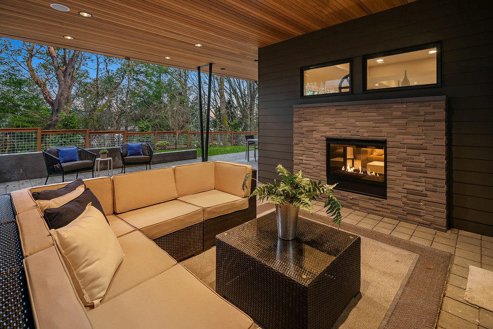 Inspiration for a contemporary concrete paver patio remodel in Seattle with a fireplace and a roof extension
