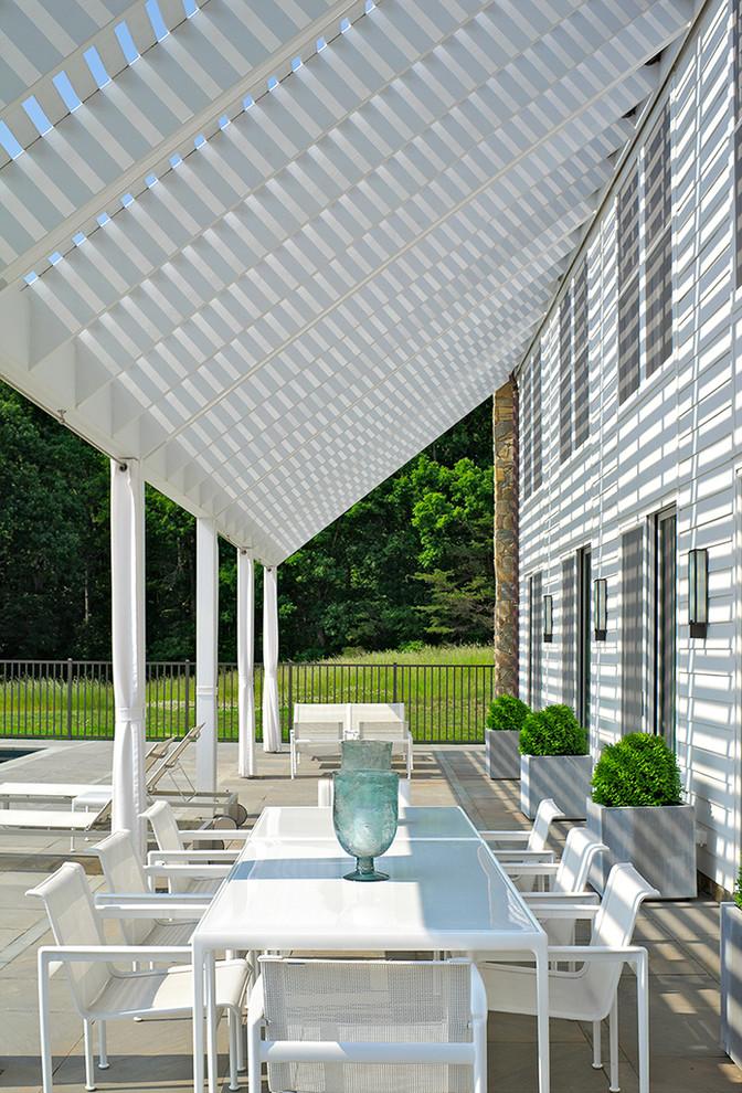Patio - modern stone patio idea in Richmond with a pergola