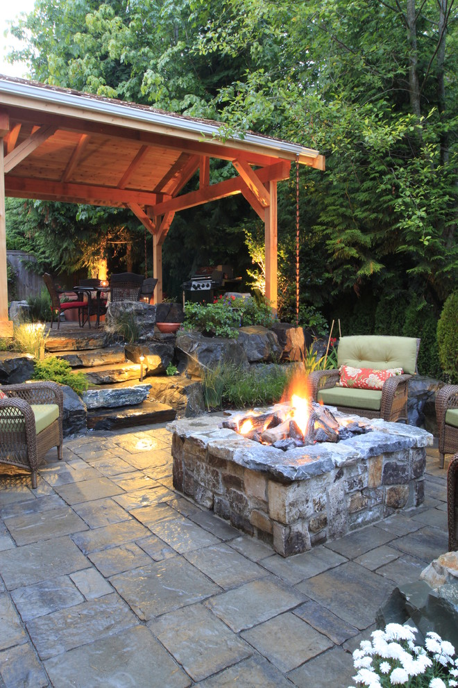 Example of a mid-sized classic backyard stone patio design in Seattle with a fire pit and a gazebo