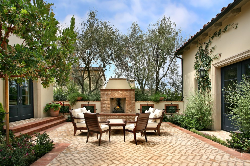Tuscan courtyard patio photo in Los Angeles with a fire pit