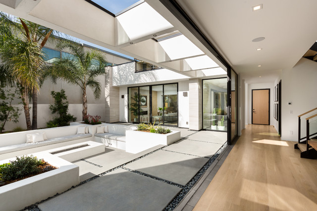 Example of a large trendy backyard concrete patio design in Los Angeles with a fire pit and a roof extension