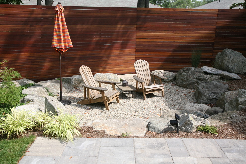 Inspiration for a mid-sized modern backyard gravel patio remodel in Boston with a fire pit