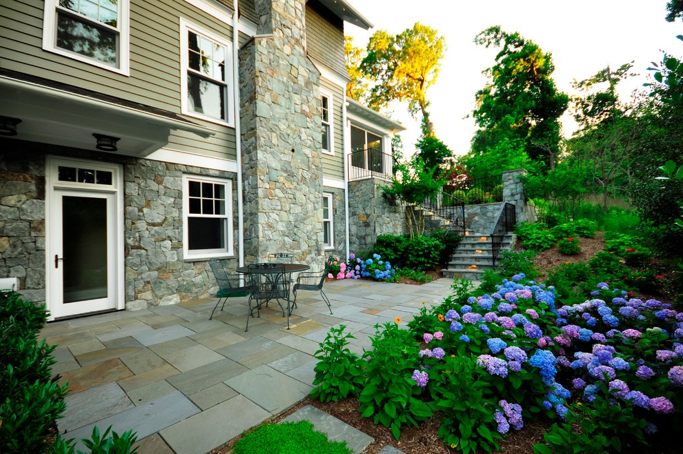 Example of a large classic backyard stone patio design in DC Metro