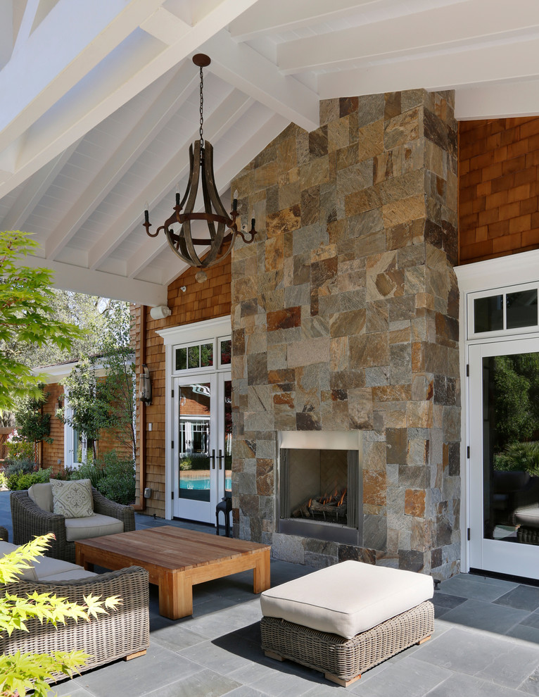 Example of a huge ornate backyard stamped concrete patio design in San Francisco with a fire pit and a roof extension