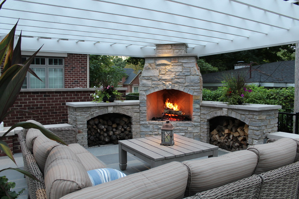 Example of a mid-sized classic backyard stone patio design in Chicago with a fire pit and a pergola