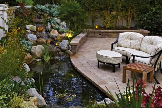 Backyard pond and patio with a rock waterfall for Rock ponds designs