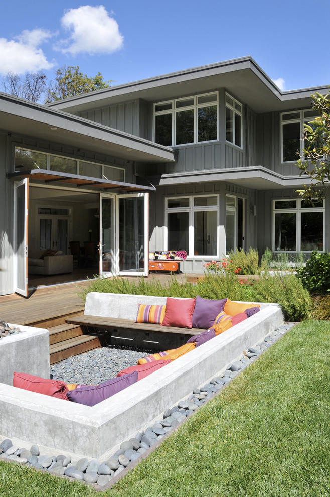 Trendy backyard patio photo in San Francisco with a fire pit, decking and no cover