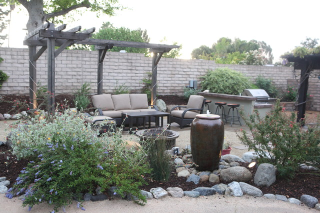 Example of a mountain style backyard stone patio fountain design in Los Angeles with a pergola