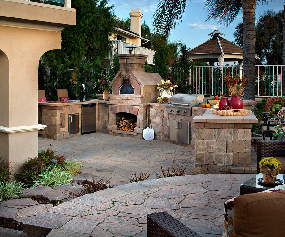 Mid-sized tuscan backyard stone patio kitchen photo in Other with no cover