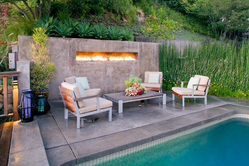 concrete pool deck with fire installation in wall.