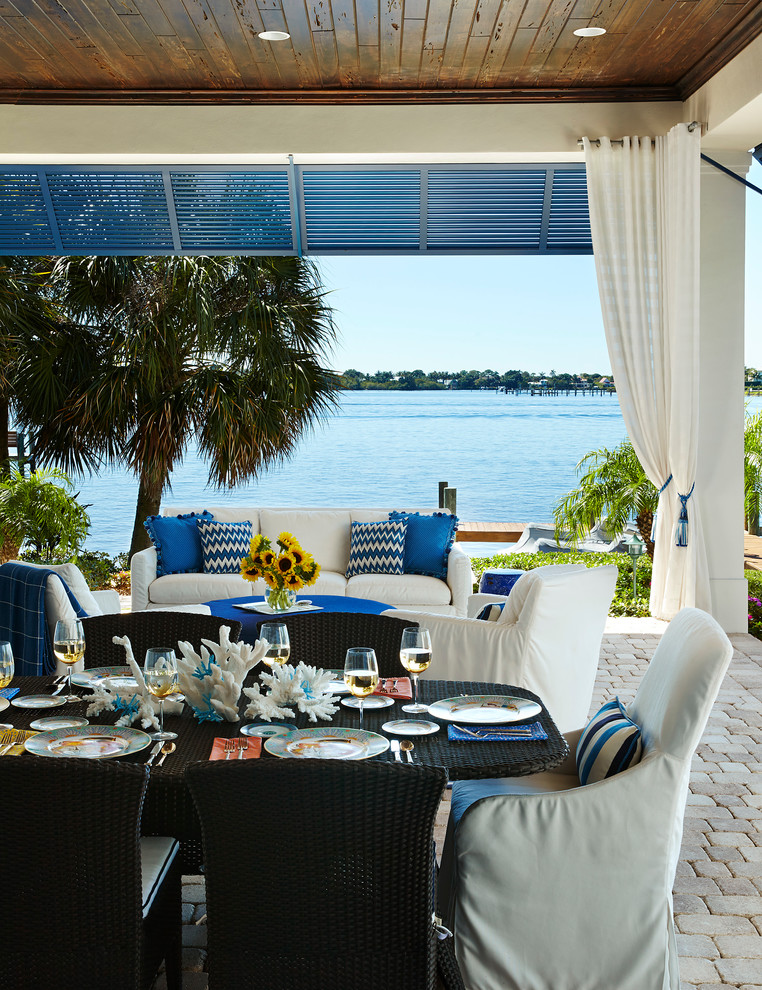Inspiration for a mid-sized coastal backyard concrete paver patio remodel in Miami with a roof extension
