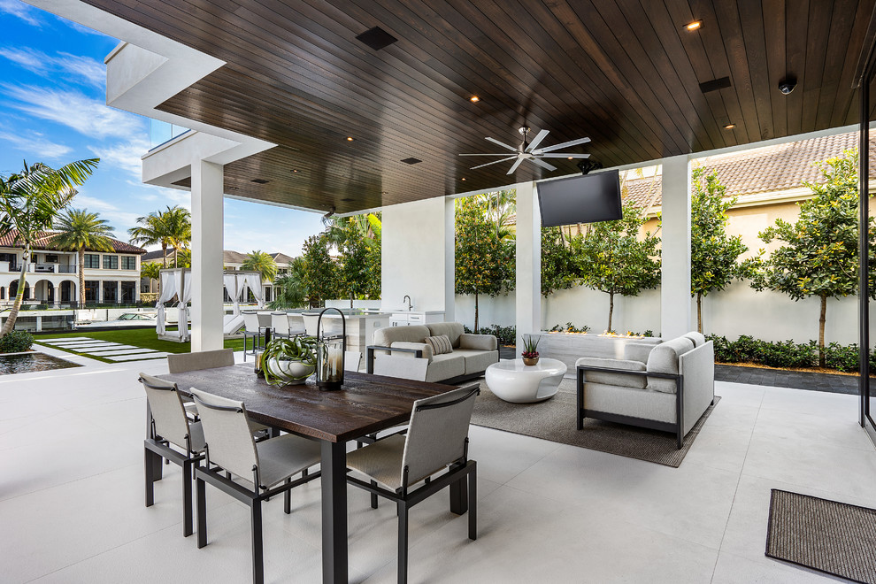 Large trendy backyard tile patio photo in Miami with a fire pit and a roof extension