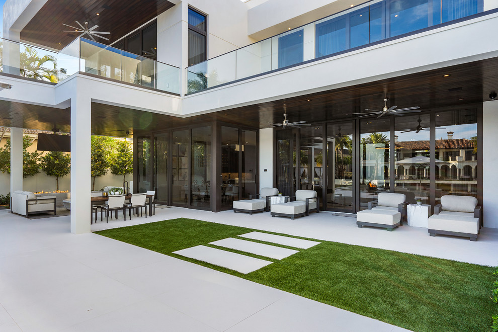 Inspiration for a large modern backyard tile patio remodel in Miami with a fire pit and a roof extension