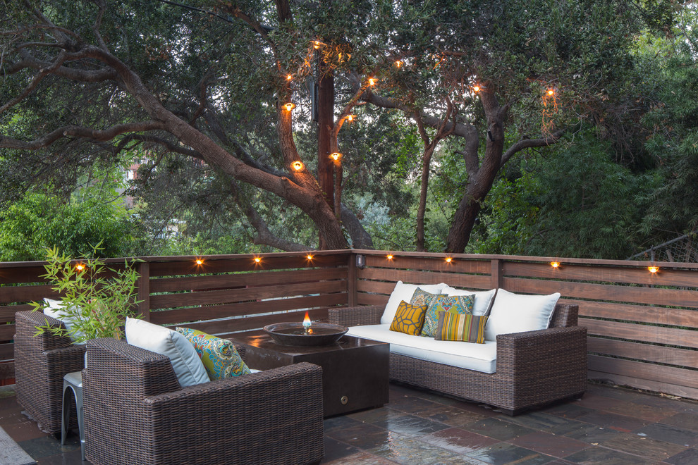 Example of an eclectic tile patio design in Los Angeles with a fire pit and no cover