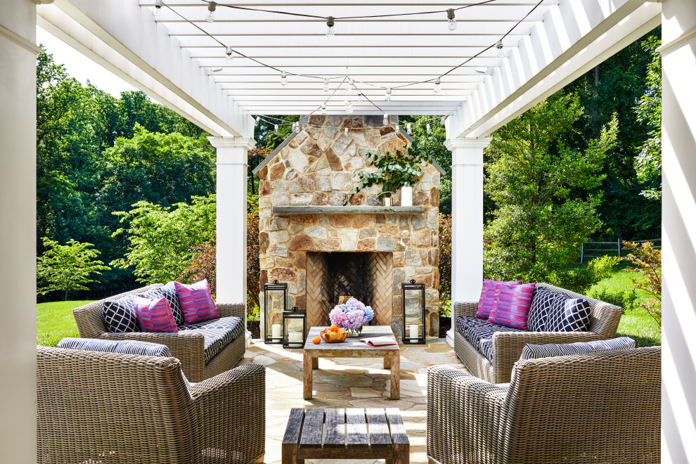 Patio - traditional stone patio idea in Baltimore with a fireplace and a pergola