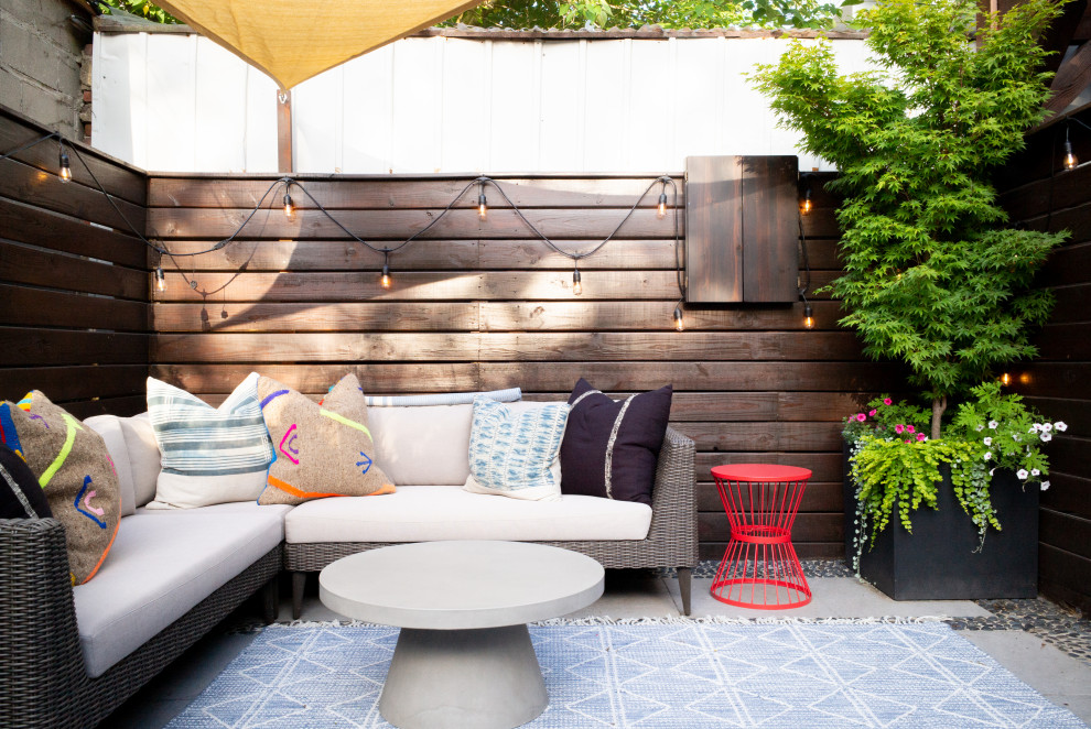 Small trendy backyard concrete patio container garden photo in New York with an awning