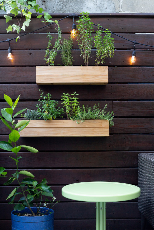 Timber planter boxes on timber wall with festive lights on patio wall