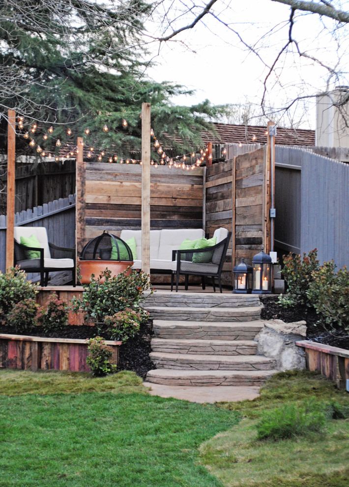 Example of a mid-sized transitional backyard patio design in Sacramento with a fire pit