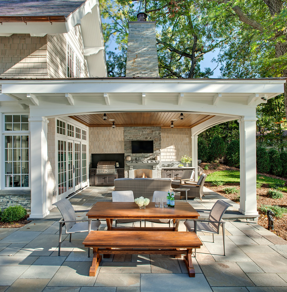 Inspiration for a timeless backyard stone patio remodel in Minneapolis with a roof extension and a fireplace