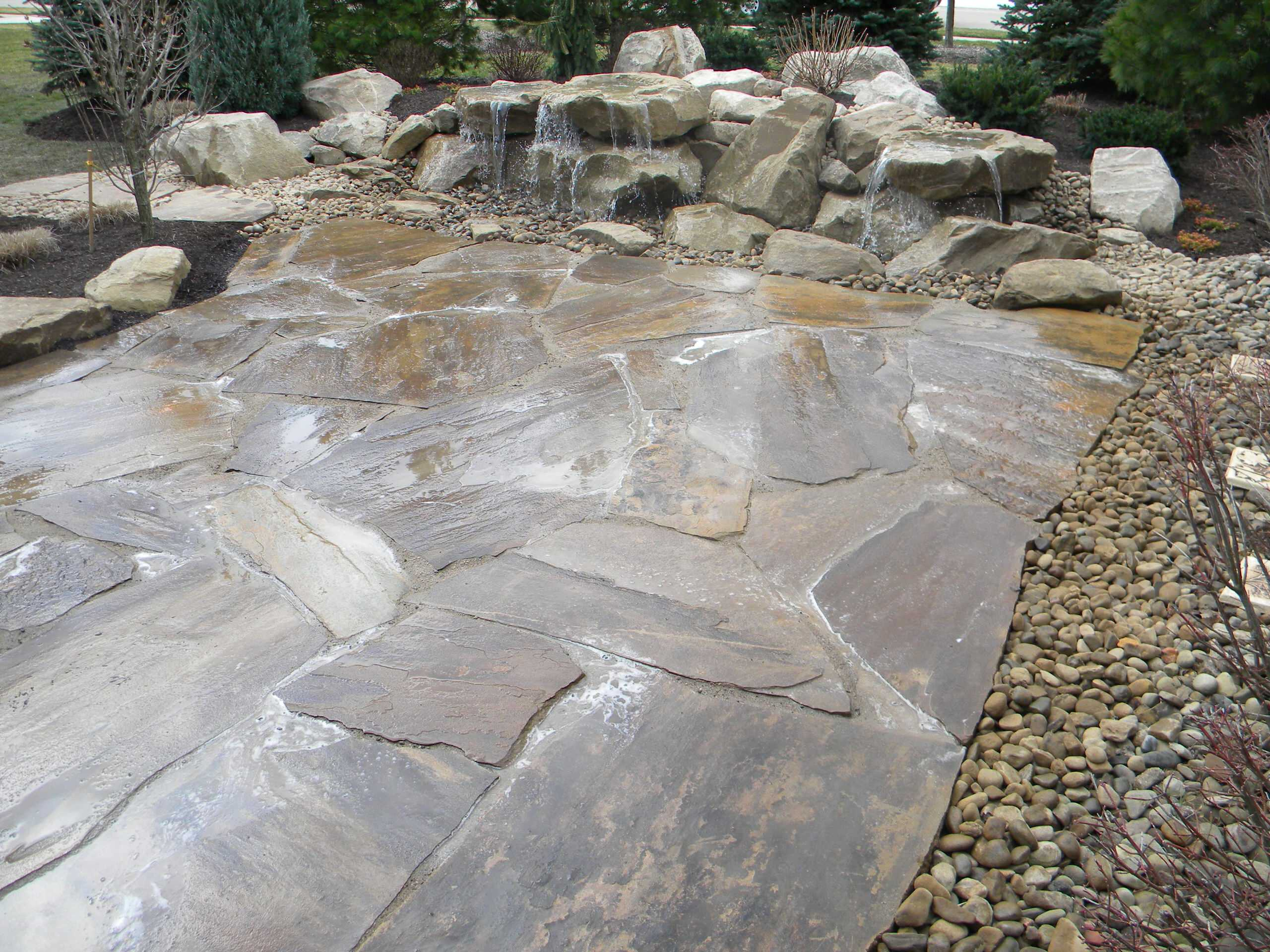 Carved stone water feature pondless and stone patio
