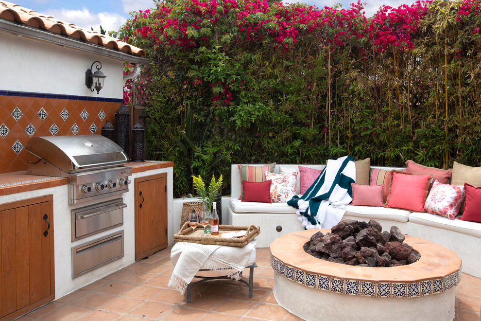 Tuscan backyard tile patio photo in San Diego with a fire pit and no cover
