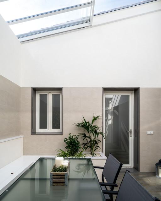 Ejemplo de patio actual, de tamaño medio, en patio trasero y anexo de casas, con jardín de macetas y suelo de baldosas