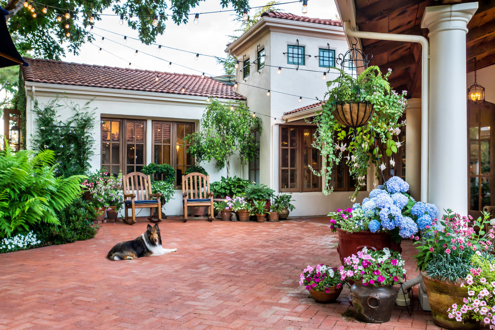 Inspiration for a large mediterranean courtyard brick patio remodel in San Francisco