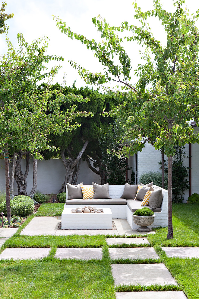 Beach style backyard concrete paver patio photo in Orange County with a fire pit and no cover